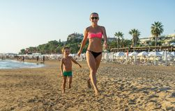 Happy little boy with young beautiful mother running on summer beach. Positive human emotions, feelings, joy. Funny cute child mak Stock Images