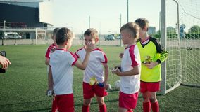 Happy little boys footballers are rejoicing by win