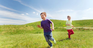 Happy little boys running outdoors Royalty Free Stock Image