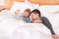 Happy little brother and sister lying in bed. Together as they cuddle under the duvet reading a tablet computer before going to sleep Royalty Free Stock Photography