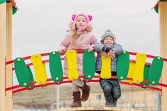 Happy little brother and sister playing in a playground stock image