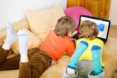 Happy little brothers, adorable kid boys watching television while lying Royalty Free Stock Photos