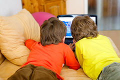 Happy little brothers, adorable kid boys watching television while lying Royalty Free Stock Photography
