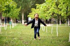 Happy little brunette boy runs in a summer park Stock Photos