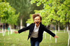 Happy little brunette boy runs in a summer park Royalty Free Stock Photography