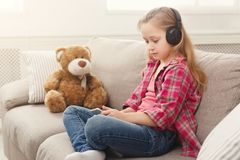 Happy little female child and her teddy bear listening to music on sofa at home Stock Photo