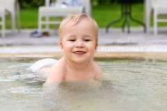 Happy little caucasian blond toddler boy swimming in wading pool on bright summer day at resort. Adorable baby enjoying outdoor stock photography