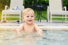 Happy little caucasian blond toddler boy swimming in wading pool on bright summer day at resort. Adorable baby enjoying outdoor stock photo
