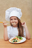 Happy little chef eating a pasta dish Stock Photography