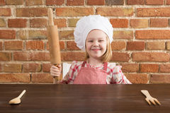 Happy little chef in the kitchen. Kid girl preparing  food, cooking Royalty Free Stock Images