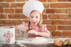 Happy little chef in the kitchen. Kid girl preparing  food, cooking Royalty Free Stock Photo