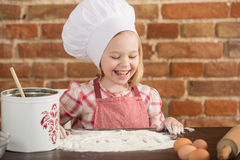 Happy little chef in the kitchen. Kid girl preparing  food, cooking Royalty Free Stock Image