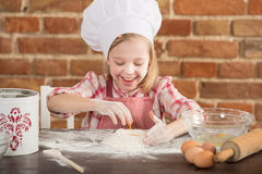 Happy little chef in the kitchen. Kid girl preparing  food, cooking Royalty Free Stock Photos