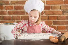 Happy little chef in the kitchen. Kid girl preparing  food, cooking Stock Photos