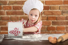 Happy little chef in the kitchen. Kid girl preparing  food, cooking Stock Images