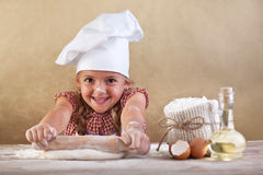 Happy little chef stretching the dough royalty free stock photo