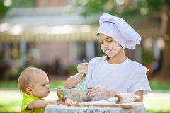Happy little chef whipping eggs in a bowl outdoors. Stock Photo