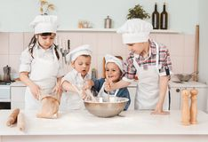 Happy little chefs preparing dough in the kitchen Royalty Free Stock Image