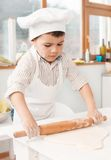 Happy little chefs preparing dough in the kitchen Stock Photo