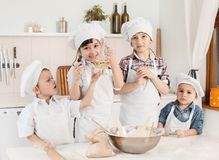Happy little chefs preparing dough in the kitchen Royalty Free Stock Photos