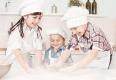 Happy little chefs preparing dough in the kitchen Royalty Free Stock Photo