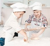 Happy little chefs preparing dough in the kitchen Stock Image