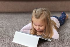 Happy little child, adorable blonde toddler girl enjoying using tablet pc stock photos