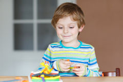 Happy little child, adorable creative kid boy playing with dough Royalty Free Stock Image