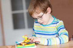 Happy little child, adorable creative kid boy playing with dough Royalty Free Stock Photos
