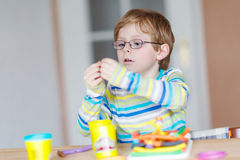Happy little child, adorable creative kid boy playing with dough Stock Photo