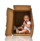 Happy little child baby girl hiding in a cardboard box having fu Royalty Free Stock Images
