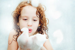 Happy little child blowing foam with her hand. Royalty Free Stock Photos