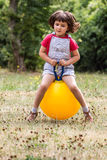 Happy little child bouncing on a jumping ball for fun Royalty Free Stock Image