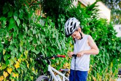 Happy little child boy in white helmet inflating tire in his bicycle royalty free stock images
