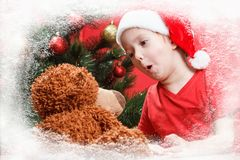 Happy little child with Christmas presents, toy teddy bear. Xmas with kids gifts and tree. Royalty Free Stock Photos