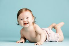 Happy little child crawling on a ground. Happy little child crawling on a ground on a blue background. Sweet infant Stock Images