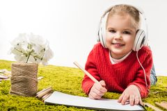 Happy little child drawing with color pencils and listening music on green soft carpet. Isolated on white royalty free stock photo
