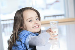 Happy little child drinking milk on a kitchen Royalty Free Stock Images