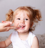 Happy little child getting her teeth cleaned with finger toothbr Royalty Free Stock Photo
