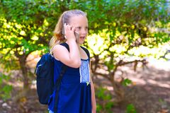 Happy little child girl go to school and talking on mobile phone at city park. stock photo