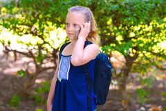 Happy little child girl go to school and talking on mobile phone at city park. stock images