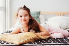 happy little child girl lying on her bed in the morning, waking up in comfortable room with modern bedlinen Stock Images