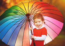Happy little child girl with multicolored rainbow umbrella in pa. Happy little child girl with multicolored rainbow umbrella on nature in the park Stock Photography