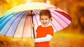 Happy little child girl with multicolored rainbow umbrella in pa. Happy little child girl with multicolored rainbow umbrella on nature in the park Stock Photo