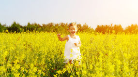 Happy little child girl running on field with yellow flowers Royalty Free Stock Images