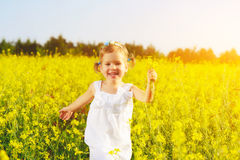 Happy little child girl running on field with yellow flowers Royalty Free Stock Photos