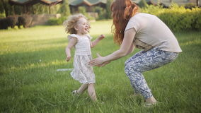 Happy little child girl running on on green meadow field to her mother stock footage
