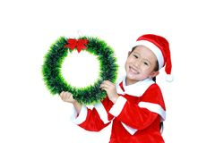 Happy little child girl in Santa costume with holding Christmas round wreath on her face on white background. Merry Christmas and. Happy New Year Concept royalty free stock image