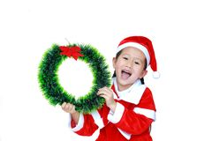 Happy little child girl in Santa costume with holding Christmas round wreath on her face on white background. Merry Christmas and. Happy New Year Concept royalty free stock photography