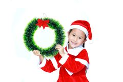 Happy little child girl in Santa costume with holding Christmas round wreath on white background. Merry Christmas and Happy New. Year Concept stock photography